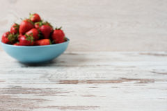 Blurred effect background. Pile of juicy ripe organic fresh strawberries in a large blue bowl. Light rustic wooden background. Royalty Free Stock Photo
