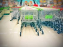 Blurred empty shopping carts green and white handles in a large supermarket; stock image