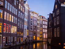 Blurred Europe city view. Colorful buildings on canal at night Stock Images