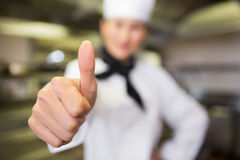 Blurred female cook gesturing thumbs up in kitchen Stock Image