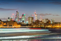 Blurred ferry light trails with London City skyline, night view Royalty Free Stock Photos