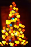 Blurred festive background made with Christmas tree and lights. New year backdrop. Royalty Free Stock Photos