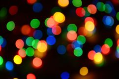 Blurred festive colorful lights over black useful as background. All main colors included. Red, yellow, green and blue.  Royalty Free Stock Photos