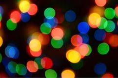Blurred festive colorful lights over black useful as background. All main colors included. Red, yellow, green and blue.  Stock Image
