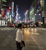 Blurred figure of a salariman as he crosses the street in Ginza Royalty Free Stock Photo