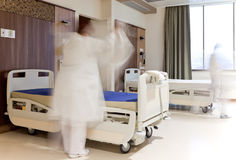 Staff fixing bed hospital room. Blurred figure of staff in medical uniform fixing bed in modern hospital room Royalty Free Stock Photo