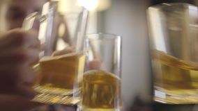 Blurred figure of woman with pigtails sitting at the bar counter with glass of beer. The girl clinking half-empty stock footage