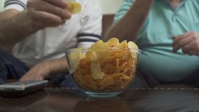 Blurred figures of two mature senior men sitting on the brown leather sofa watching TV. Big bowl with chips is on the. Table, hands of friends taking chips from stock video footage