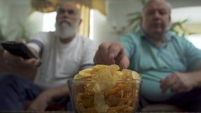 Blurred figures of two mature senior men sitting on the brown leather sofa watching TV. Big bowl with chips is on the. Blurred figures of two mature senior men stock video