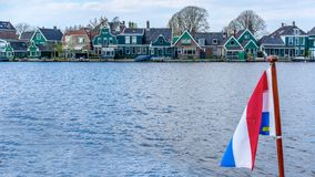 Blurred flag of the Netherlands against the background of a traditional Dutch village stock photos