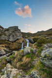 Blurred flowing waterfall in the Alps with colorful sky and clouds at twilight, among rocks, boulders and grass. Little stream in Royalty Free Stock Images
