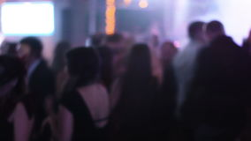 Blurred footage of crowded hall at night club with dancing young people around students hanging out at their prom night