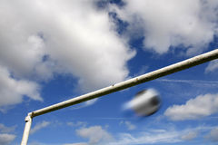 Blurred football and goalpost against a cloudy sky Stock Photography