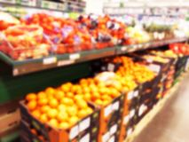 Blurred fresh fruits and vegetables at retail store. Abstract background of supermarket. Grocery market blurred background. Fruits. In store racks. Interior royalty free stock images