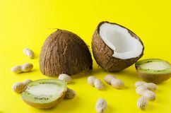 Coconut, peanuts, kiwi fruit on yellow brigh surface -concept of traveling, vacation at the exotic countries royalty free stock images
