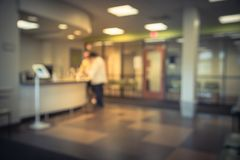 Blurred front desk area of clinical laboratory office with table. Blurred lobby/front desk area of clinical laboratory services office. Customer check-in on stock image