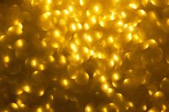 Blurred golden background with circle sparkling lights. Shiny yellow glittery bokeh of christmas garland. Dark backdrop.  stock image