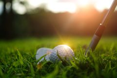 Golf ball and golf club in beautiful golf course at sunset background. Blurred golf ball and golf club in beautiful golf course at sunset background stock photography