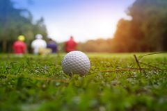 Golf ball on green in beautiful golf course with sunset. Golf ba. Blurred golf ball on green in the evening golf course with sunshine in thailand stock photo