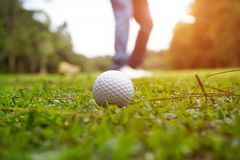 Golf ball on green in beautiful golf course with sunset. Golf ba. Blurred golf ball on green in the evening golf course with sunshine in thailand royalty free stock images