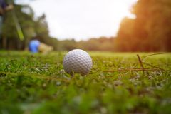 Golf ball on green in beautiful golf course with sunset. Golf ba. Blurred golf ball on green in the evening golf course with sunshine in thailand stock photos