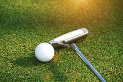 Blurred golf club and golf ball close up in golf coures at Thail. Blurred golf club and golf ball close up in grass field with sunset. Golf ball close up in golf Royalty Free Stock Photo