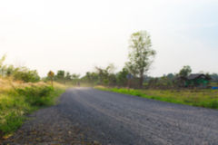 Blurred gravel road in the countryside of chiangmai thailand with green grass and beautiful evening sun light Stock Images
