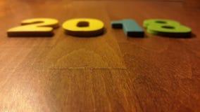 Blurred ha colorato le figure per formare il numero 2018 su fondo di legno Immagini Stock