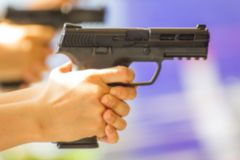 Blurred Hand of Woman hold a gun ready to shoot stock images