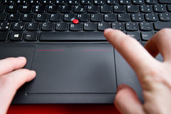 Blurred hands above the keyboard of red colored laptop Stock Photos