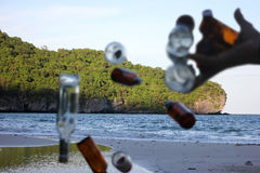 Blurred hands littering the bottle on the beach. Stock Photography