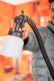 Blurred handsome smiling handyman holding in his hands the painting spray gun, an wearing a gray jacket in a blurred Stock Image