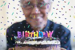 Blurred happy old man showing birthday cake. With colorful candles and confetti sprinkles stock photography