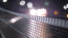 Cars driving at night, view through the net. Blurred headlights of cars driving on the road at night, view through the net stock video footage