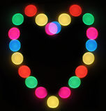 Blurred Holiday lights heart. Blurred holiday lights shaped as heart on dark background Royalty Free Stock Photography