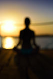 Blurred image back woman sitting in a lotus pose on the wooden p. Lanks, sunset, vertical Stock Photo