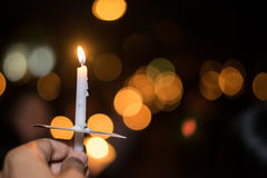 Blurred image for background of hand with candle memorable for King Bhumibol Adulyadej of thailand Stock Photo