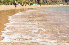 Blurred image of beach with foamy waves. Blurred image of beach with soft foamy waves. People walking and relaxing. Idyll travel concept Stock Images