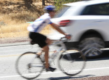 A blurred image of a bicycle and car on the road. An abstract blurred photo of a bike rider and car on the street together Royalty Free Stock Photo