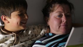 Blurred image of boy and his mother Reading book before the sleep Focusing on child legs Sweet Family stock video