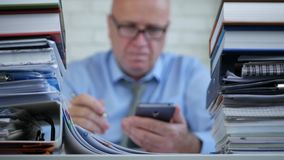 Blurred image with a businessman using cellphone and writing documents.  stock video