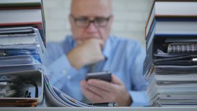 Blurred Image With Businessperson In Office Text Using Cellphone stock photo