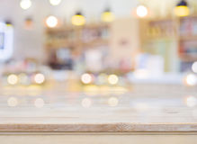 Blurred image of cafe interior with wooden table in front Royalty Free Stock Photo