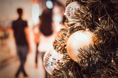 Blurred image of Christmas Decorations In Christmas Tree with copy space of blur light boken and people background. vintage tone royalty free stock images