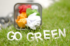 Blurred image of crumple paper in thrash can with alphabet GO GREEN Stock Image