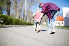Blurred image of father, son ,. Blurred image of father with son and run bike in park stock photo