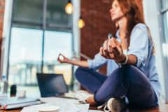 Blurred image of female student meditating on desk in classroom calming mind with her hand in focus.  Royalty Free Stock Photos