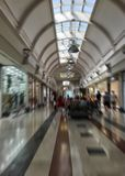 Blurred image of indoor mall gallery with fashion stores on both sides. For a shopping concept. with people stock photos