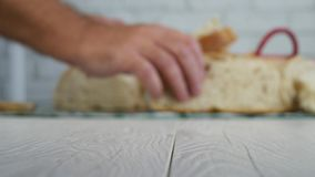 Blurred Image with Man Cutting in Slices a Fresh Bread and Put on the Basket stock footage