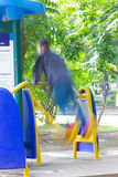 Blurred image of a man exercising on equipment in a park in Thai Stock Images